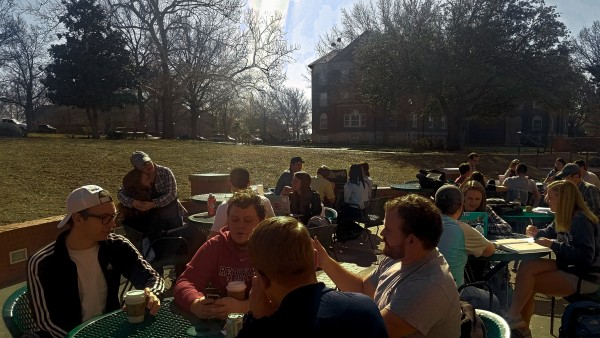Multiple students talking and enjoying the warm spring day.